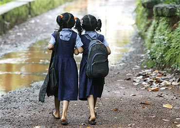 Two girls walk to their school in a Kerala village