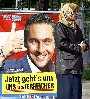 A woman stands in front of an election banner of the Freedom Party, which reads Now it is about us Austrians, in Vienna