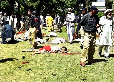 Police and residents stand over victims at the site of the suicide bomb attack
