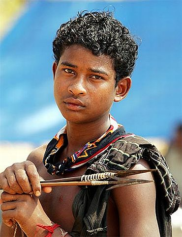 A tribal teenager holds a bow and arrows at a relief camp in Dharbaguda