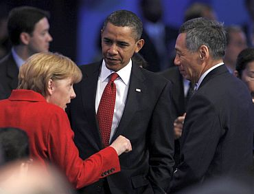 US President Obama listens to German Chancellor Merkel alongside Singapore's PM Lee