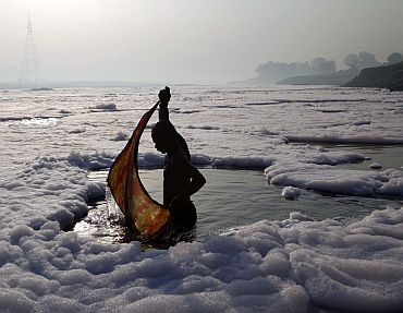 A devotee wraps his cloth after a ritual dip in the polluted Yamuna river in New Delhi