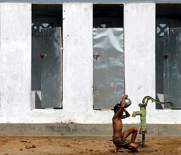 A boy takes bath under a tubewell in a village on the outskirts of Nagapattinam