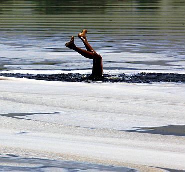 A boy swims in the polluted Yamuna river in New Delhi