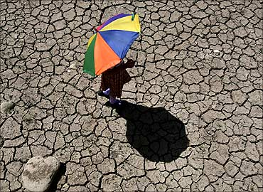 A schoolgirl crosses a dry pond on the outskirts of Jammu