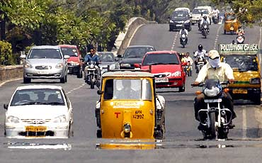 Vehicles move through a mirage of heat in Hyderabad