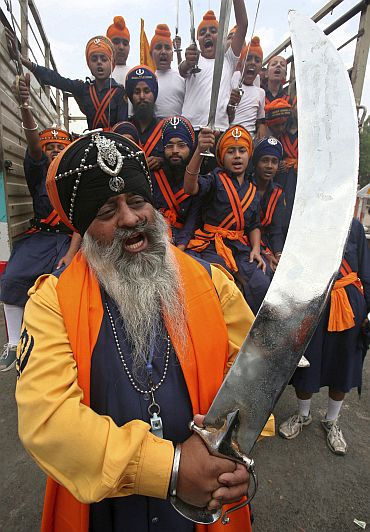 'Nihangs' or Sikh warriors hold swords and shout slogans during a religious procession ahead of the Baisakhi festival in Chandigarh