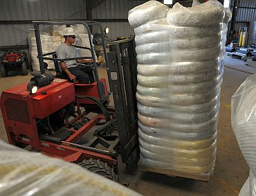 reston Kott of US Environmental Services moves oil absorbent boom into a warehouse at a pollution control staging area