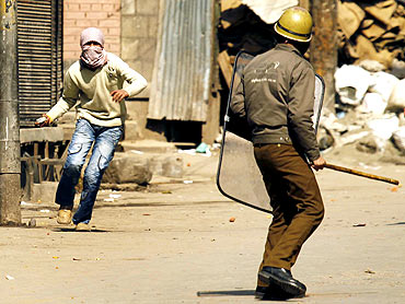 A policeman confronts a stone throwing Kashmiri protester in Srinagar, February 20