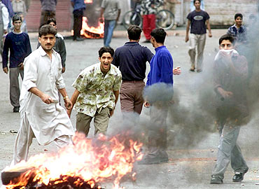 Protesters shout slogans during a clash with police in Srinagar