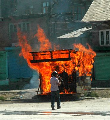 A cameraman runs to safety. In the background, a vehicle set ablaze by a mob