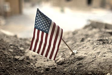 An American flag is placed in a dirt-filled barrier outside the headquarters of 3rd Platoon near Kandahar
