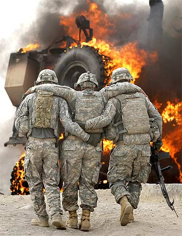 An injured soldier from the US army is assisted past a burning vehicle