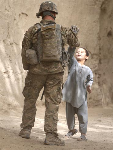 A US trooper high-fives a boy during a patrol through the village of Tabinolye in Arghandab