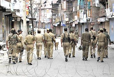 Police patrol a curfew-bound locality in Srinagar