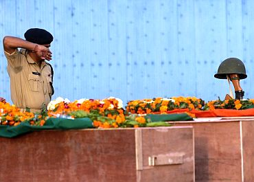 A CRPF jawan pays his last respects to colleagues who died in a Naxalite attack in Chhattisgarh
