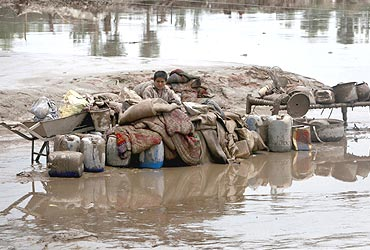 A boy sits next to his belongings while waiting to be evacuated from floods in Nowshera, located in Pakistan's northwest Khyber-Pakhtunkhwa Province, on August 2