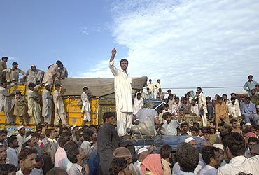 A man requests aid for flood victims amidst passengers and cargo trucks which were halted by townsmen requesting relief supplies in Nowshera on August 2