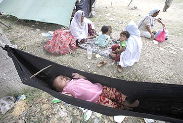 A child lay crying in a hammock after flood victims shifted to camps to take refuge after their homes were destroyed in Nowshera on August 3