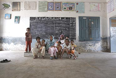 A family living near the Sindh river took shelter in a class room in Sukkur, in Pakistan's Sindh province, on August 3