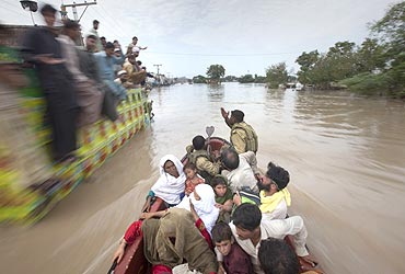 A family rescued by army soldiers pass a cargo truck with men on top taking shelter from heavy floods in Nowshera, located in northwest Pakistan on July 31