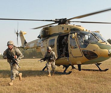 US Army soldiers exit an Indian army HAL Dhruv advanced light helicopter from the 201st Army Aviation Squadron during static load training on Camp Bundela, India