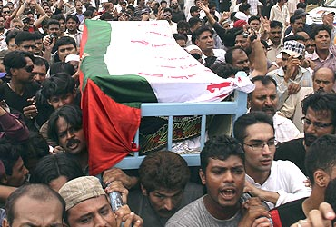 Supporters carry the flag-draped coffin of MQM leader Raza Haider