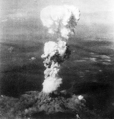 At the time this photo was made, smoke billowed 20,000 feet above Hiroshima while smoke from the burst of the first atomic bomb had spread over 10,000 feet on the target at the base of the rising column. August 5, 1945. Two planes of the 509th Composite Group, part of the 313th Win