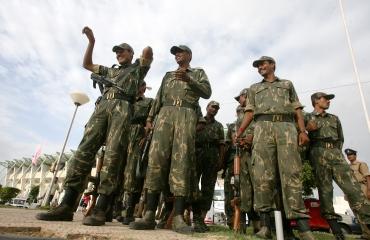 Paramilitary personnel survey a site