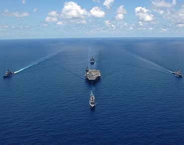 US Navy ships assigned to the USS George Washington Carrier Strike Group sail in formation