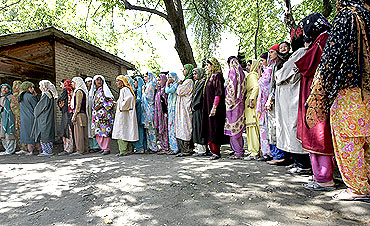 Kashmiri voters stand in line to cast their votes during the general election