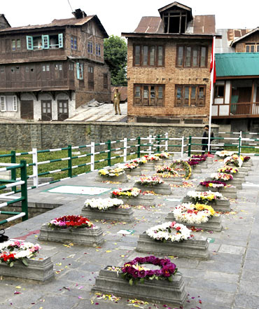 Policemen guard grave stones at the martyrs' graveyard in Srinagar