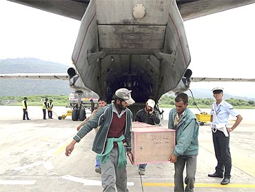 Men carry the body of a victim who was killed in flash floods in Leh