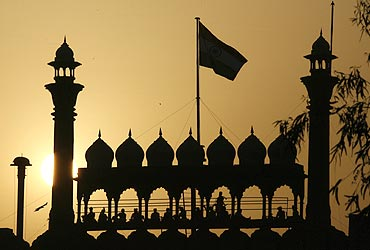 Indian soldiers are silhouetted against the rising sun at the historic Red Fort in New Delhi