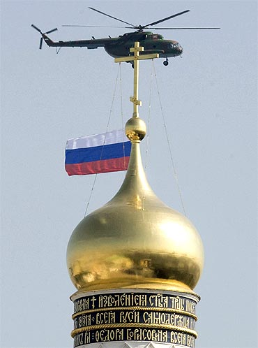 A military helicopter carrying the Russian national flag flies past the Bell Tower of Ivan The Great in the Kremlin