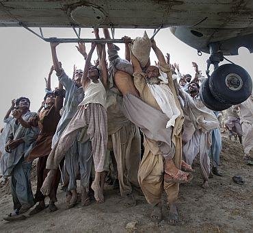Marooned flood victims looking to escape grab the side bars of a hovering Army helicopter which arrived to distrib