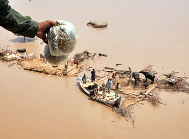 Families marooned by flood waters recieve food from an Army helicopter in the Rajanpur district of Pakistan's Punjab province