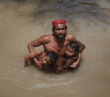 A man wades through flood waters towards a naval boat while evacuating his children in Sukkur, located in Pakistan's Sindh province