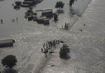 Residents stand near the path of flowing flood waters the Muzaffargarh district of Pakistan's Punjab province