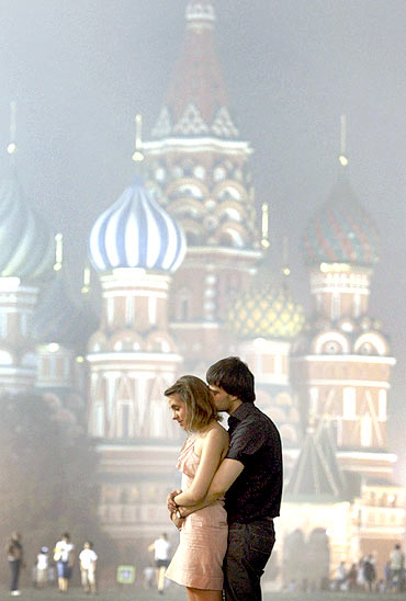A couple stands in front of the St Basil's Cathedral shrouded in smog in Moscow
