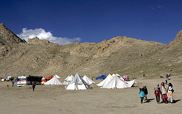 Children, victims of the flash flood, walk past relief tents in Leh