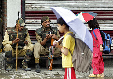 Kashmiri children carrying umbrellas walk past policemen during a shutdown