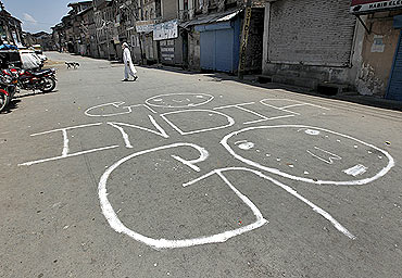 A Kashmiri man crosses a deserted road marked with graffiti