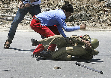 A protester hits a policeman during a protest march