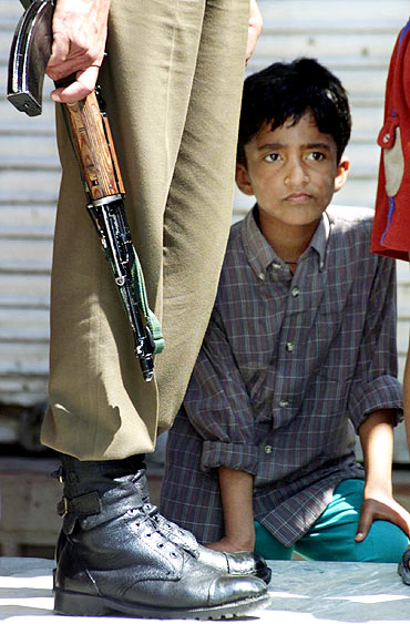 A youngster peers from behind a securityman in Maisuma, Srinagar