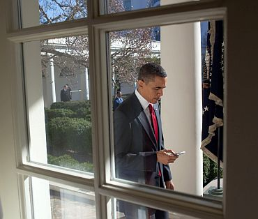 Obama checks his BlackBerry as he walks along the Colonnade to the Oval Office