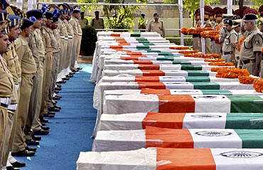 CRPF personnel pay their last respects near the coffins of policemen who died in a Naxal attack
