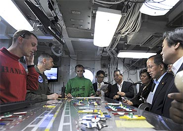 US officals speak to South Korean Defense Minister Tae Young Kim (2nd R) and other ministers aboard USS George Washington in July, 2010