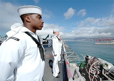 American sailors man the rails of the USS George Washington aircraft carrier as the ship arrives in Busan on July 21, 2010