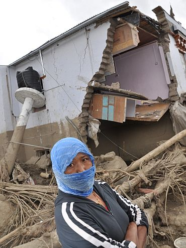 A villager beside her destroyed house